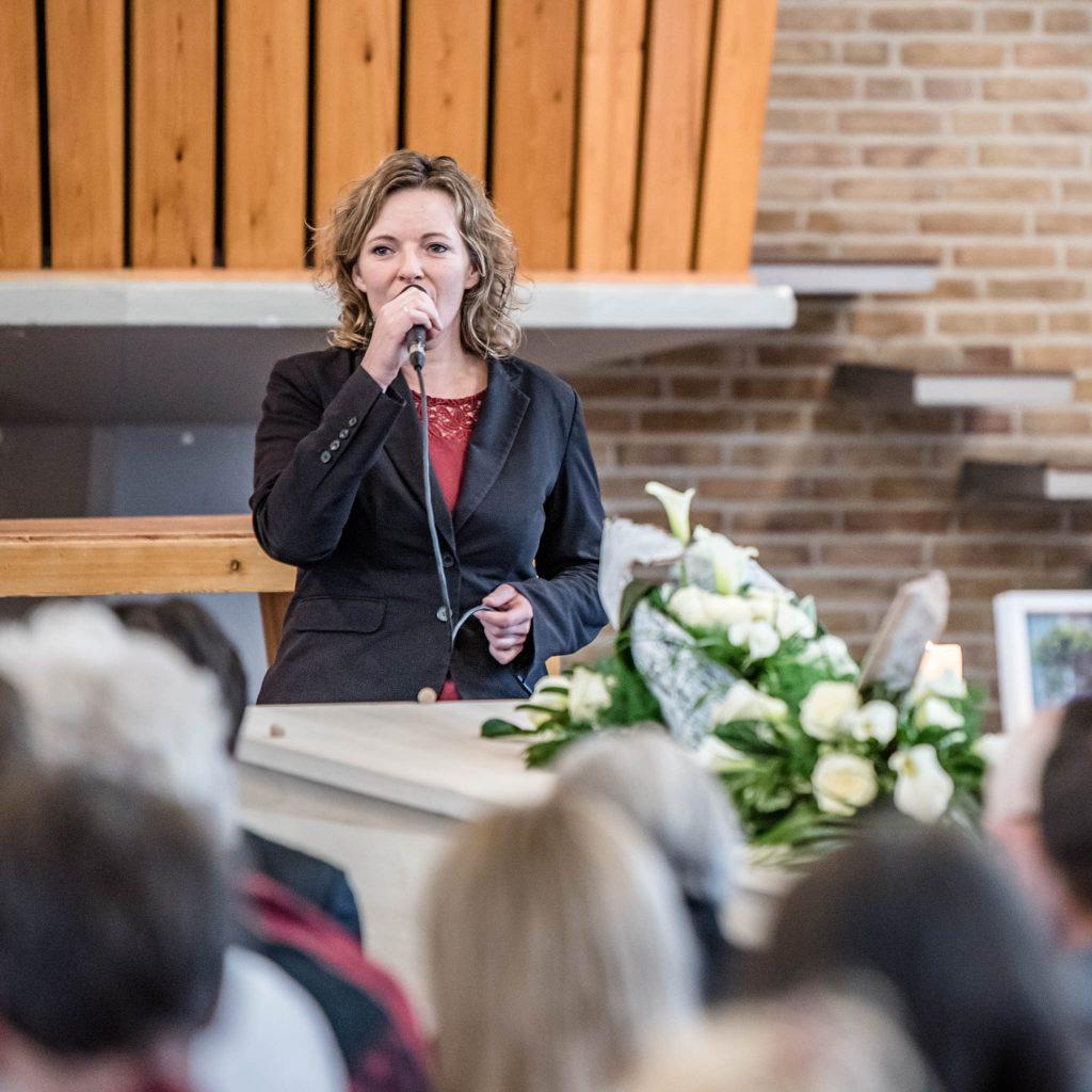 vrouw spreekt tijdens uitvaartplechtigheid