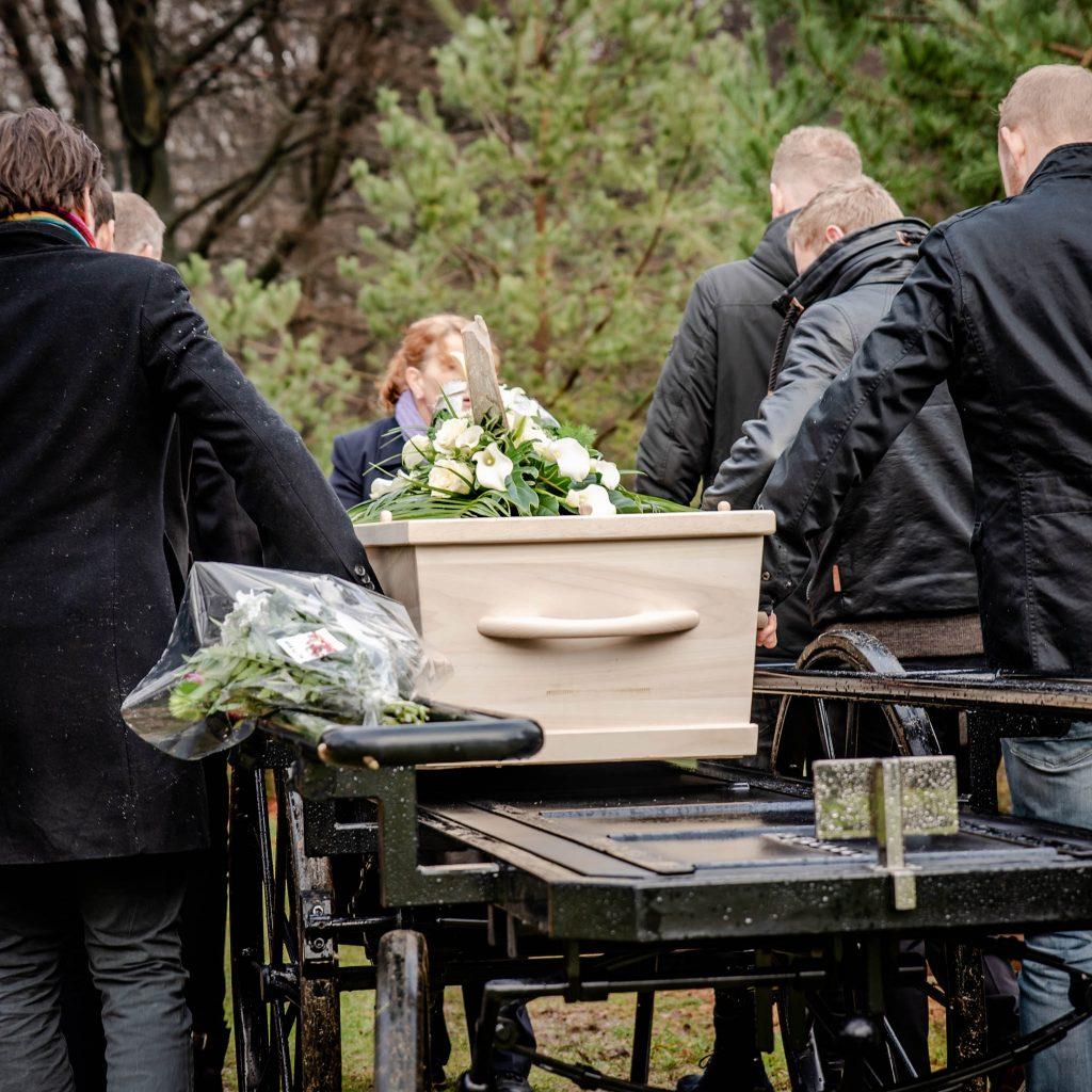 kist wordt van draagbaar getild op begraafplaats